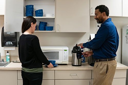 A woman putting away dishes and a man pouring himself coffee talk to each other in a kitchen.